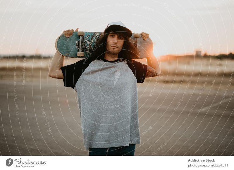 Cooler selbstbewusster Teenager mit Skateboard vor der Kamera Hipster cool Mann Stil tausendjährig ländlich Land Streetstyle Verschlussdeckel Generation