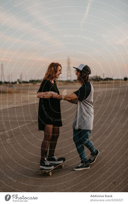 Teenager hilft seiner Freundin beim Schlittschuhlaufen auf der Straße Skateboard lernen Paar Zusammensein Spaß üben Glück abstützen Hilfsbereitschaft heiter