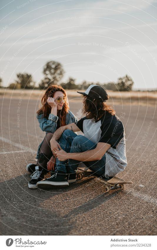 Schlittschuhläufer sitzen auf leerer Landstraße und plaudern im Sonnenlicht Paar Teenager Skater Straße ländlich Zusammensein Generation Sport Landschaft