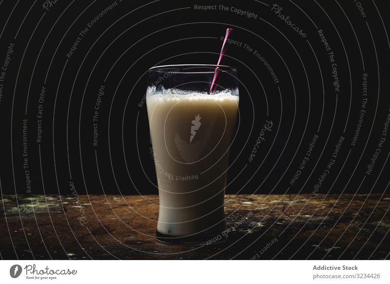 Glas Milch auf dem Tisch melken hoch weiß hell Stroh gestreift Kontrast minimalistisch frisch Cocktail Milchshake trinken Getränk Erfrischung Lebensmittel