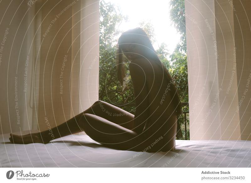 Nackte Frau auf Bett sitzend nackt sinnlich jung Verlockung Körper ruhen sich[Akk] entspannen Reling Balkon Garten sonnig tagsüber brünett Dame sexy Anruf