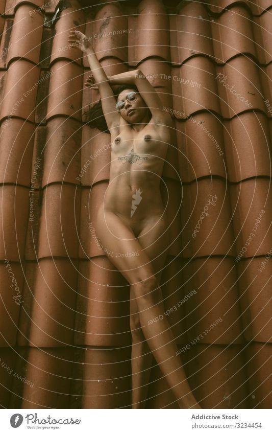 Nackte Frau auf dem Dach liegend nackt sinnlich angehobene Arme ethnisch gekachelt Haus jung Verlockung Körper ruhen sich[Akk] entspannen Brust brünett Dame