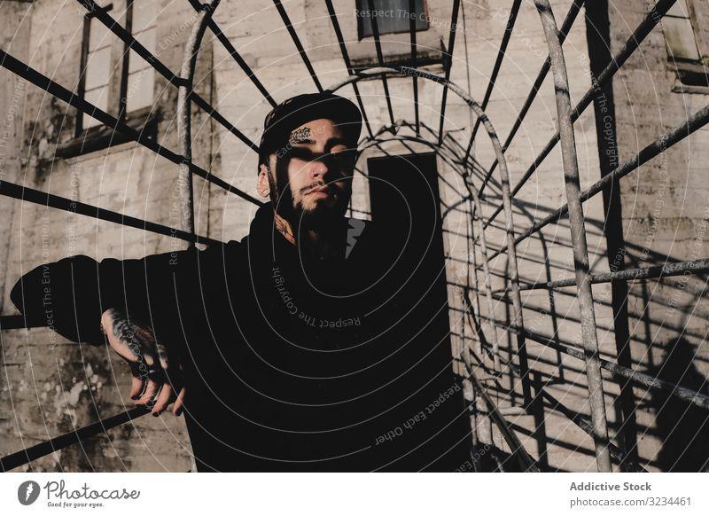 Moderner Typ in trostlosem Gebäude Mann urban modern stylisch desolat Reling fettarm jung Lifestyle männlich cool bärtig Tattoo ruhen sich[Akk] entspannen