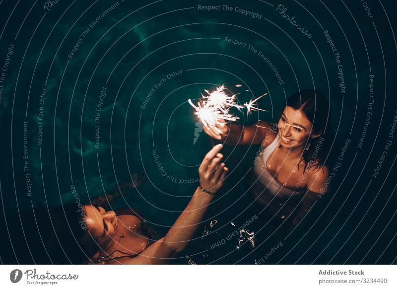 Fröhliche Freunde, die in der Nähe des Pools funkeln Wunderkerze Party Nacht Brandwunde Feier jung Menschengruppe Spaß Frauen dunkel Licht Flamme Wasser Hof