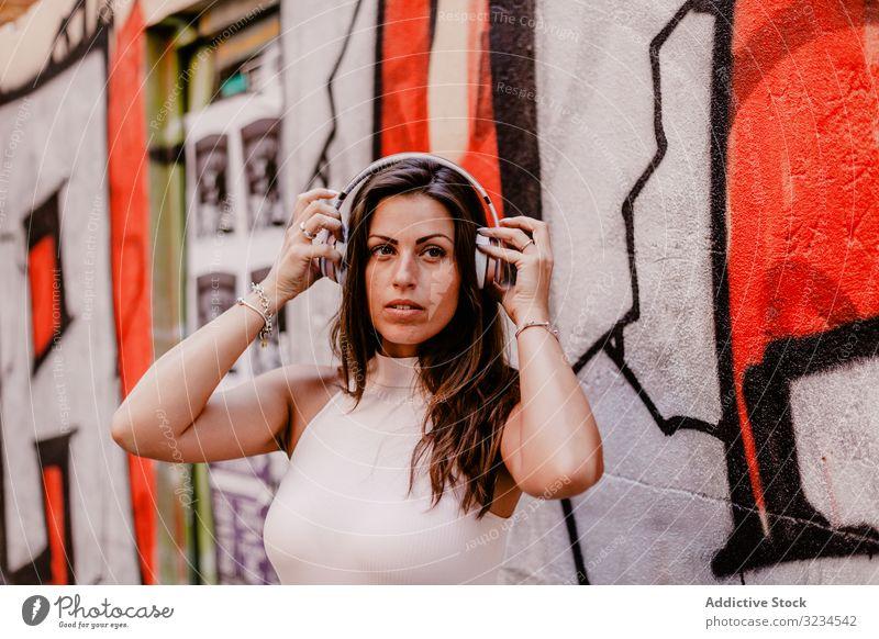 Frau, die Musik hört und ein Smartphone benutzt Kopfhörer hören Sommer Graffiti Beton Straße urban Streetstyle Grunge soziale Netzwerke Lächeln Glück Apparatur
