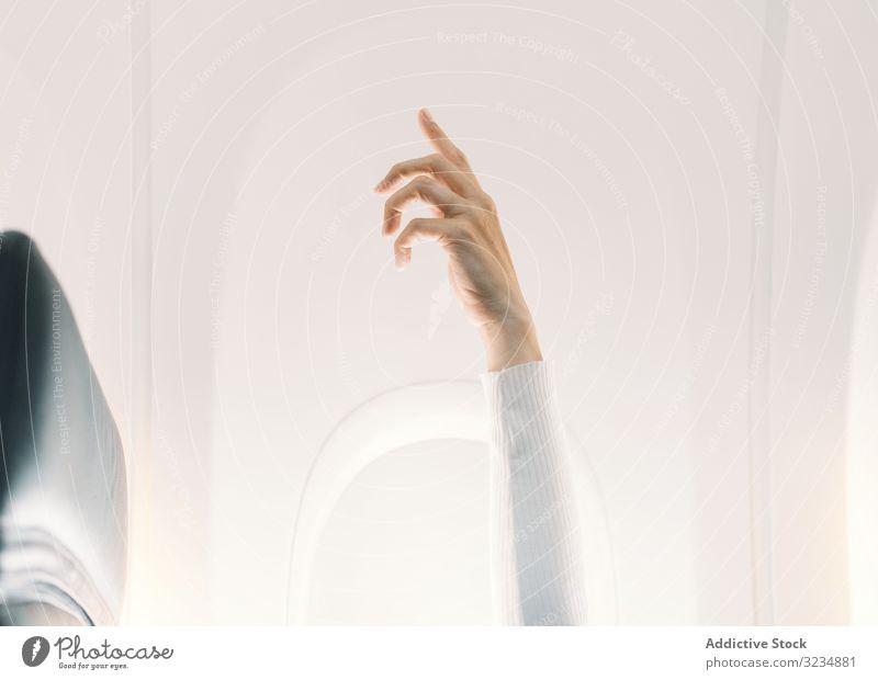 Person in weißem Pullover hebt die Hand im Flugzeug Ebene Licht Salon Fliege Aufmerksamkeit Erhöhung Fluggerät Ausdruck reisen Erwachsener Konzept Windstille