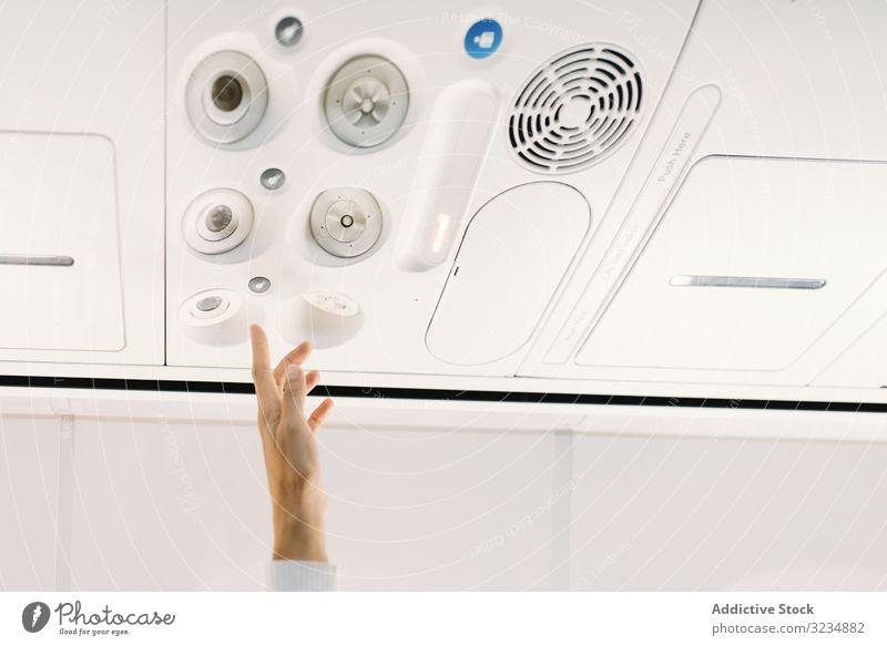 Person, die den Knopf an der Schalttafel des Flugzeugs drückt Schaltfläche Ebene Licht Salon Fliege Aufmerksamkeit Hand Erhöhung Fluggerät Stewardess