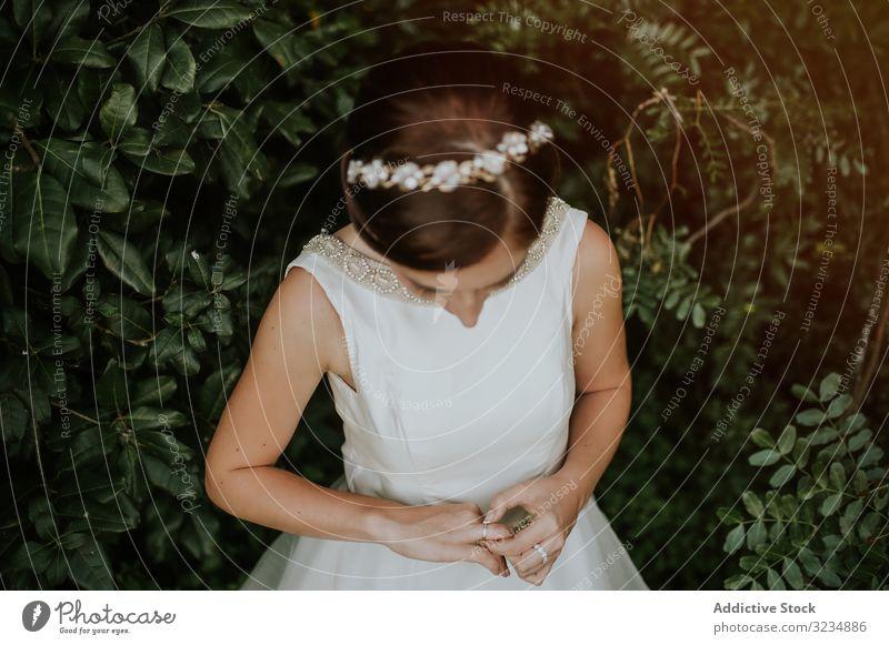 Braut in bezauberndem Kleid bewundert Fingerring im Garten charmant Diamant Ring Hochzeit Schmuck Frau hochzeitlich schön weiß Diadem Ehefrau Festakt elegant