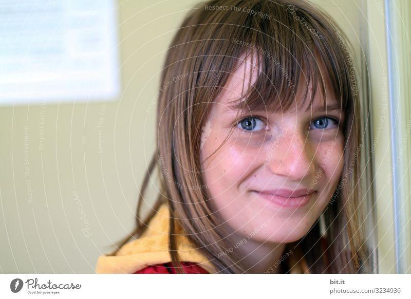 fröhliches, glückliches Mädchen mit Pony und blauen Augen, lehnt an einer Wand von einem Gebäude, und schaut natürlich mit Lächeln in die Kamera. Bildung Schule