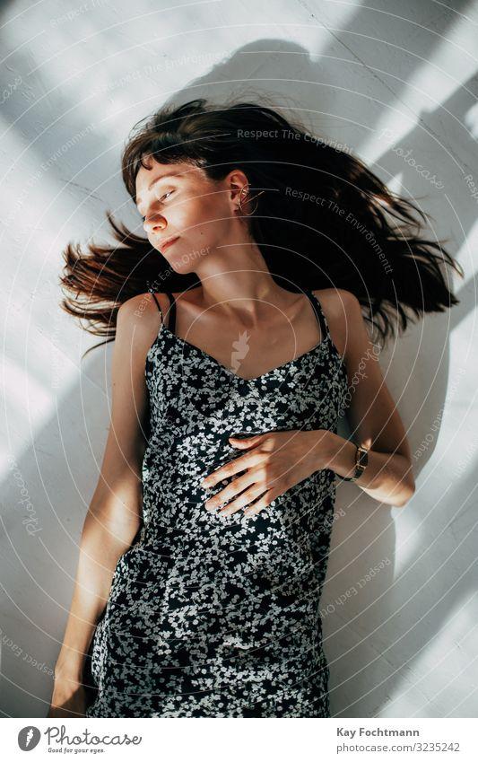 schöne brünette Frau, die auf dem Boden ihrer Wohnung liegt, um sich zu entspannen attraktiv Schönheit braun braune Haare Windstille sorgenfrei lässig Kaukasier