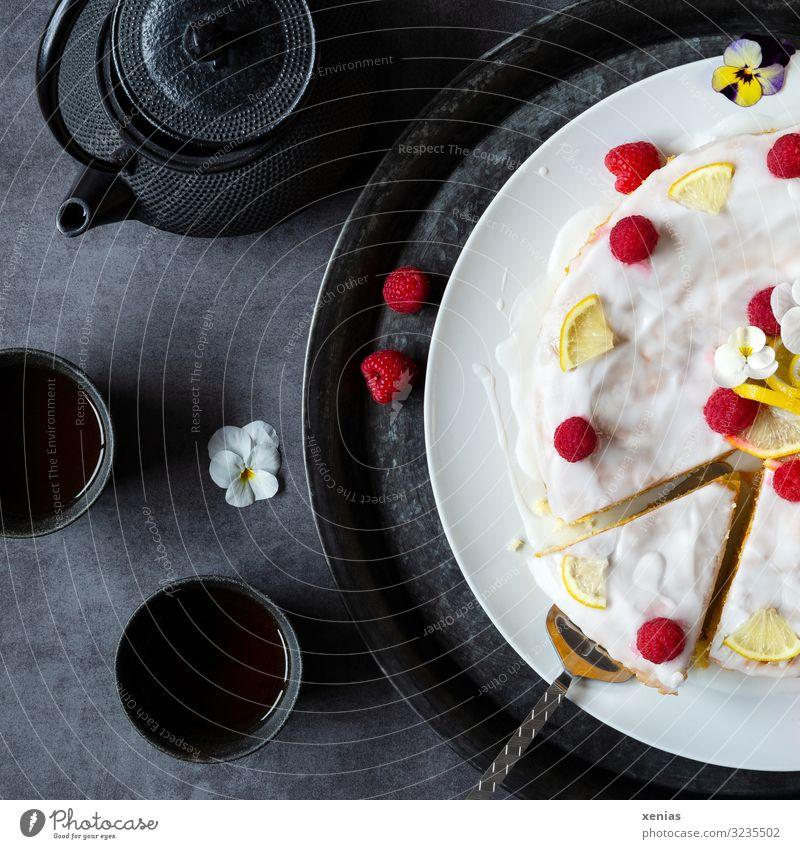 Tee mit Kuchen - heller lasierter Kuchen mit Himbeeren, Zitronen und Stiefmütterchen dazu schwarzes Teegeschirr Süßwaren Zitronenkuchen Zuckerguß Kaffeetrinken