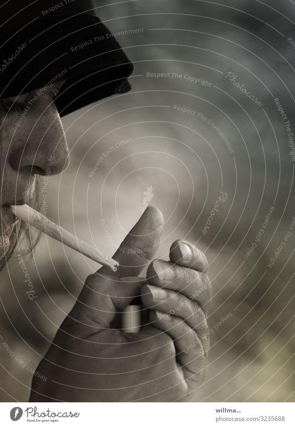 Frau mit Hut raucht selbstgedrehte Zigarette Rauchen Tabakwaren Joint Profil Schlapphut anzünden Feuerzeug Nikotin gesundheitsschädlich Gedeckte Farben