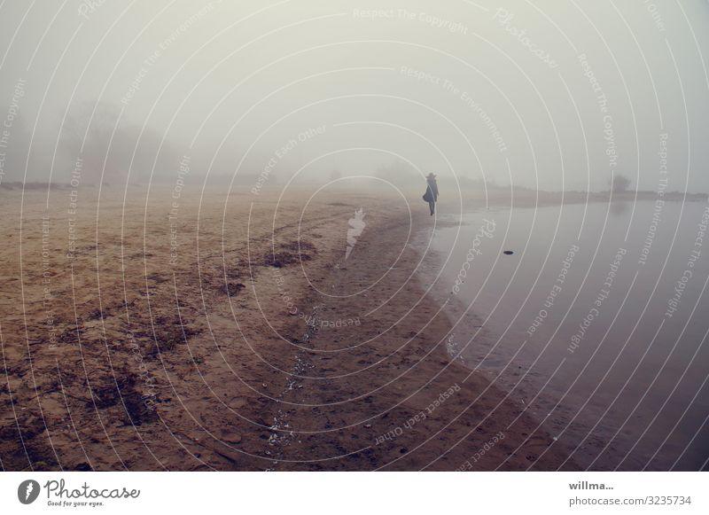 elegante Dame mit Hut im Nebel am Seeufer trüb neblig-trüb Küste Mensch feminin Frau Mantel einzeln Spaziergang Sandstrand Strand schlechtes Wetter Dümmer See