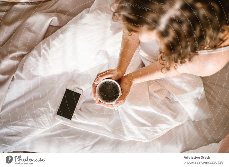 Frau mit Heißgetränk und Smartphone im Bett Kaffee verwenden Nachricht heimwärts Text Information prüfen Fokus teilen Browsen trinken leerer Bildschirm Surfen