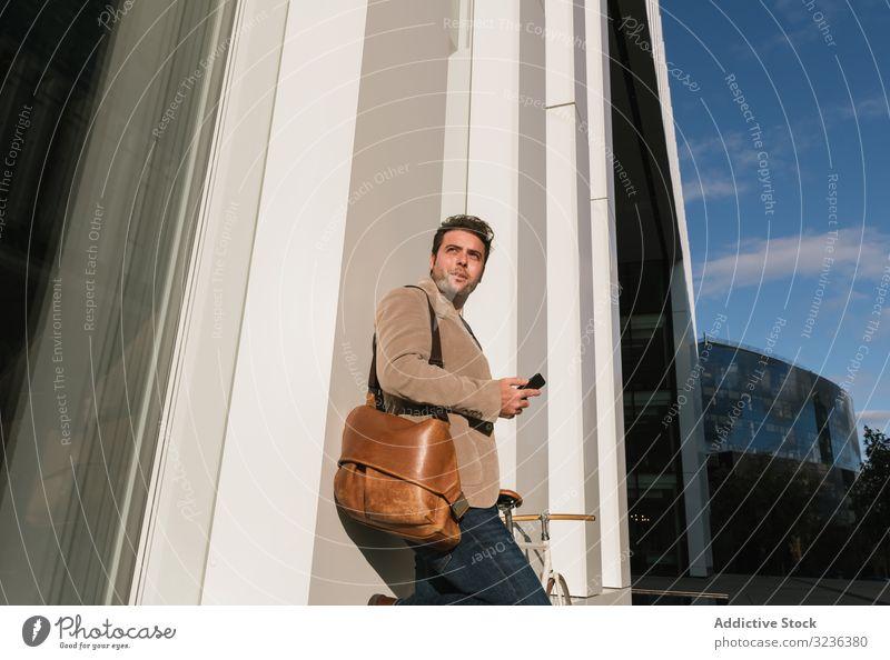 Geschäftsmann mit Smartphone lehnt sich an Gebäude auf Stadtstraße an Großstadt Straße fettarm Wand Stadtzentrum Business männlich professionell Unternehmer