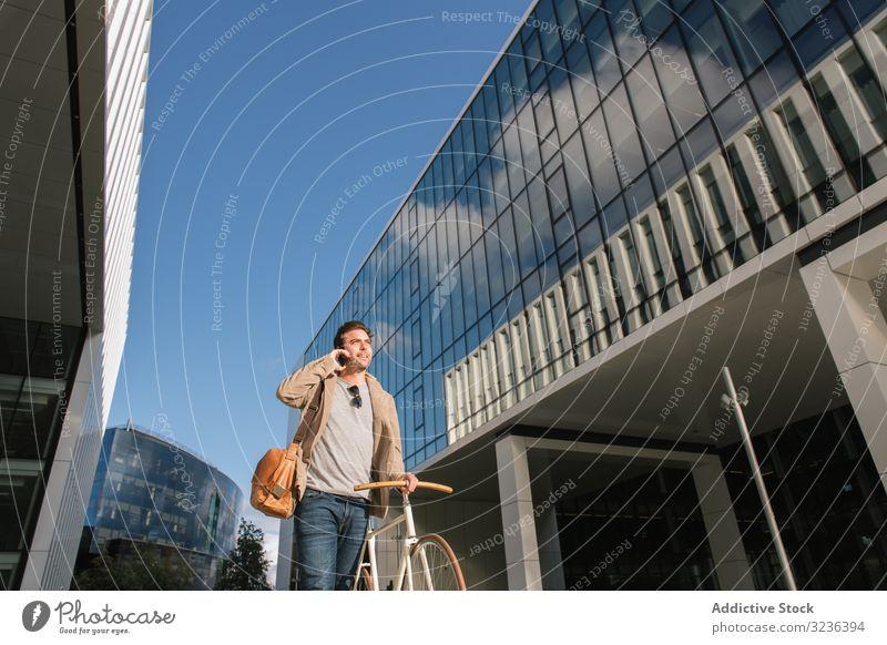 Mann telefoniert, während er vor einem modernen Gebäude in der Innenstadt steht Smartphone Handy Straße Wolkenkratzer urban reden Fahrrad besinnlich Versand