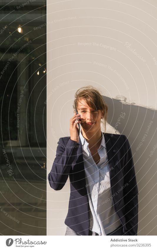 Fröhliche Managerin spricht mit Smartphone auf der Straße Geschäftsfrau Großstadt reden Wand fettarm positiv modern Lächeln Erwachsener Business Gebäude Frau