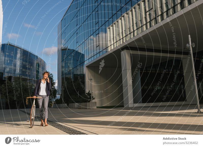 Fröhlicher Manager mit Fahrrad auf Smartphone Geschäftsfrau Straße Großstadt reden Spaziergang positiv modern Lächeln Erwachsener Business Gebäude Frau elegant