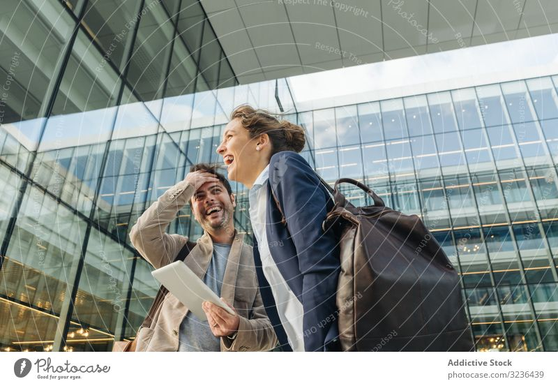Fröhliche Kollegen verwenden Tabletten nach der Arbeit Geschäftsleute Straße benutzend Lächeln soziale Netzwerke Gebäude Mann Frau Zusammensein Paar Büro lässig