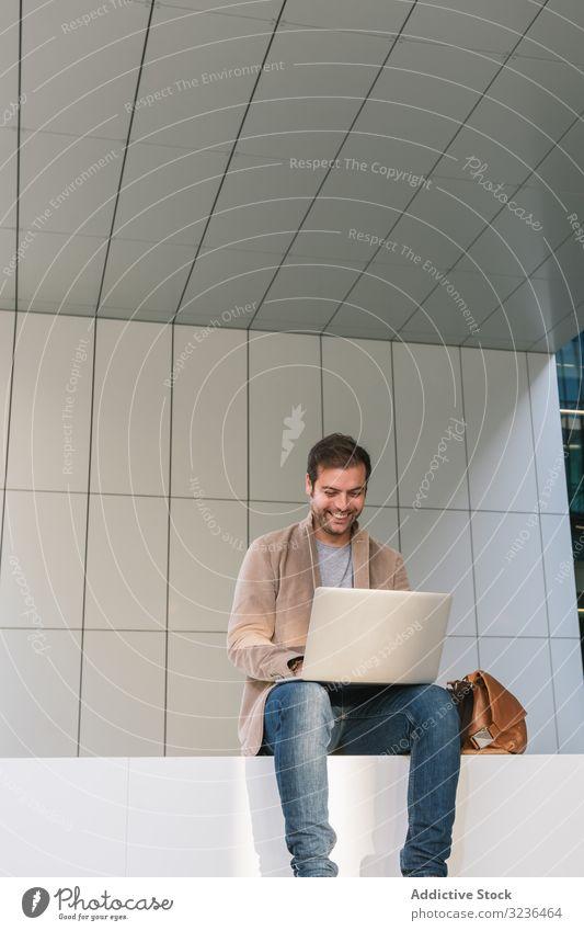 Fröhlicher Geschäftsmann mit Laptop auf der Straße Großstadt benutzend Lächeln sitzen Gebäude Stadtzentrum Business männlich Erwachsener lässig professionell