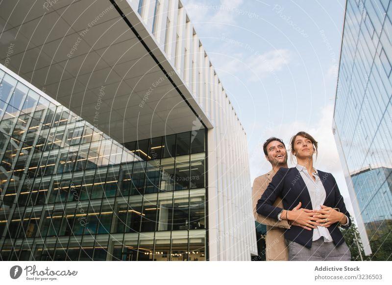 Geschäftsleutepaar vor zeitgenössischem Gebäude Straße Spaziergang Arbeit Lächeln Mann Frau Kollege Zusammensein Paar Mitarbeiterin Büro Business Großstadt