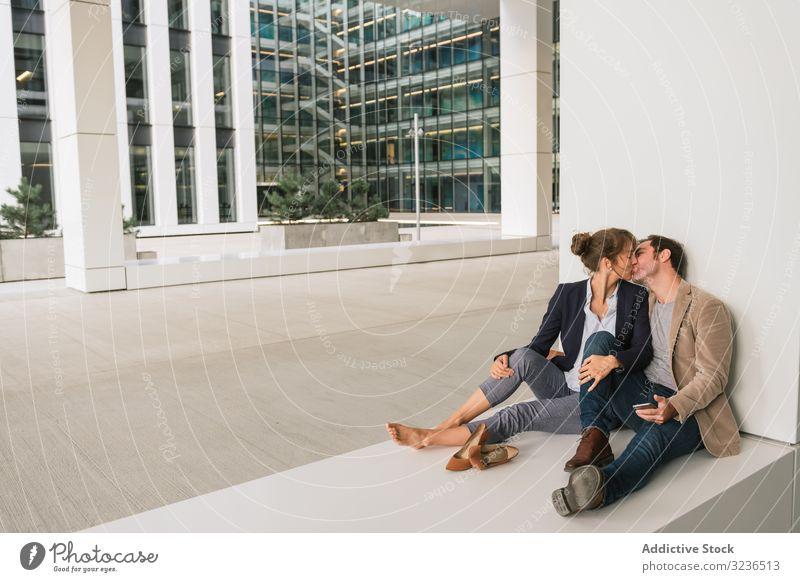 Geschäftsleute umarmen sich und nutzen Smartphone auf der Straße Paar Umarmung benutzend soziale Netzwerke Gebäude sitzen ruhen Großstadt Business Zusammensein