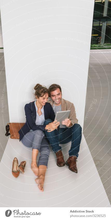 Geschäftsleute, die auf der Straße Tabletten umarmen und benutzen Paar Umarmung benutzend soziale Netzwerke Gebäude sitzen ruhen Großstadt Business Zusammensein