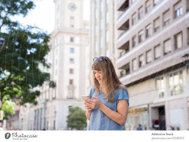 Frau mit Brille mit Smartphone im Freien Großstadt heiter lässig Sonnenbrille Straße Nachricht Lifestyle Tippen benutzend Mobile Apparatur SMS urban Antwort