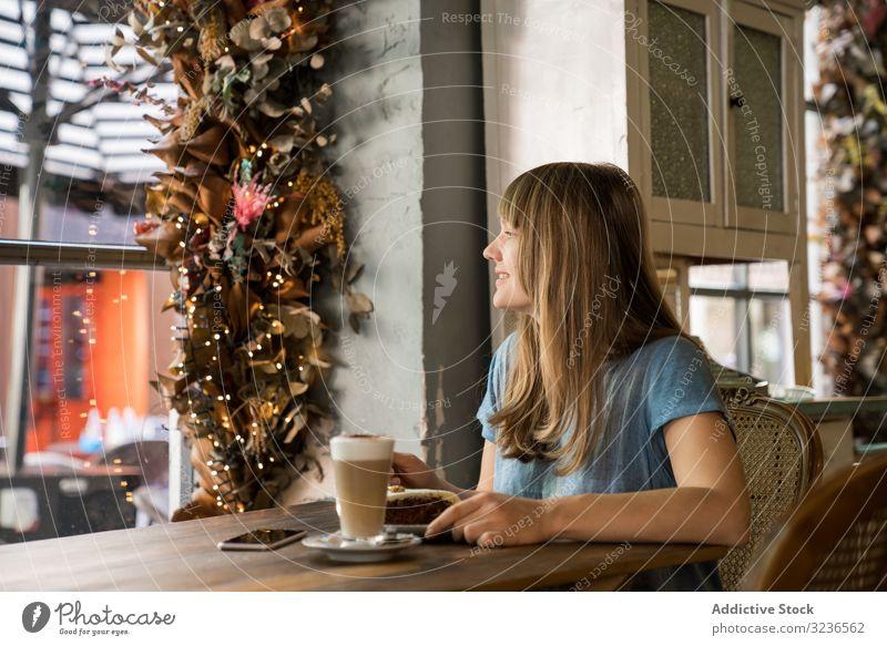 Fröhliche Frau benutzt Telefon im Café Smartphone Kaffee Lifestyle jung Mobile Glück heiter Lächeln Lachen Freizeit trinken lässig Restaurant Sitzen Halt