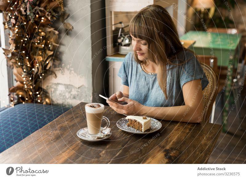 Frau benutzt Smartphone im Cafe Café benutzend Tippen Kaffee Lifestyle jung Mobile Nachricht heiter Freizeit trinken SMS lässig Restaurant Sitzen Halt