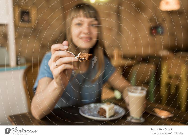 Frau hält Löffel mit Tortenscheibe Kuchen Café Scheibe Geben Spielfigur Kaffee Lifestyle jung Glück Angebot geschmackvoll heiter Freizeit trinken lässig