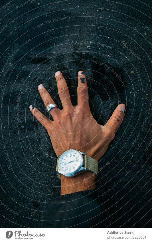 Person legt Hand mit Uhr auf schwarzen Sand Zeigeruhr Strand MEER Feiertag Urlaub zuschauen berührend Island Sport schön Sanduhr Gesundheit sich[Akk] entspannen