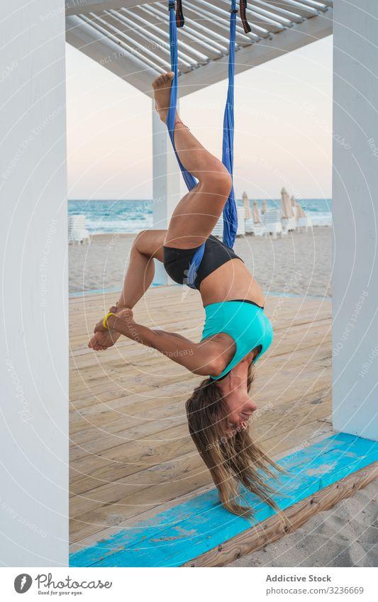 Entspannte Frau, die Luftyoga macht, den Kopf nach unten hängend und das Bein berührend Luft-Yoga herunterhängen Übung Gleichgewicht akrobatisch Fitness