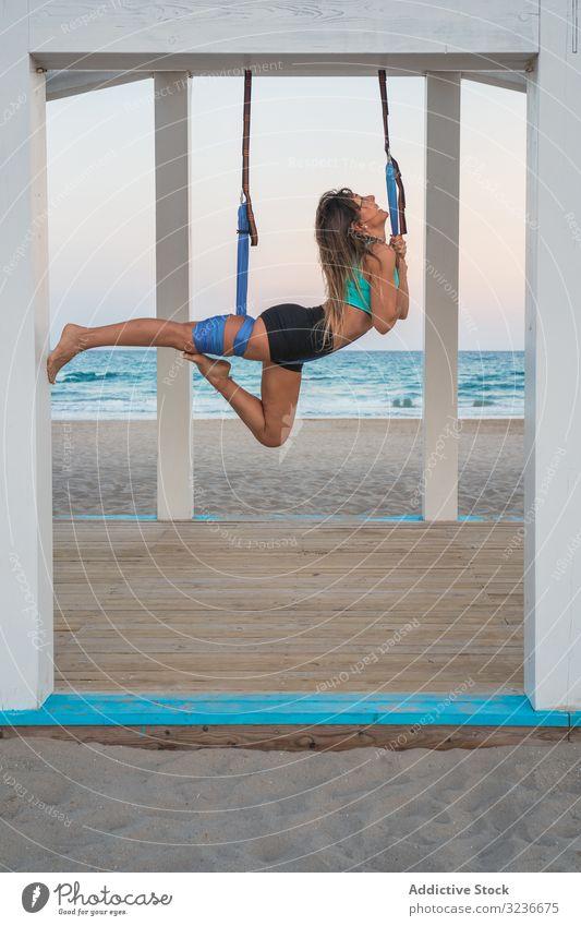 Fröhliche Frau streckt Bein auf blauer Hängematte für Luftyoga auf Holzbühne Luft-Yoga Übung Gleichgewicht akrobatisch Fitness Antigravitations-Yoga jung