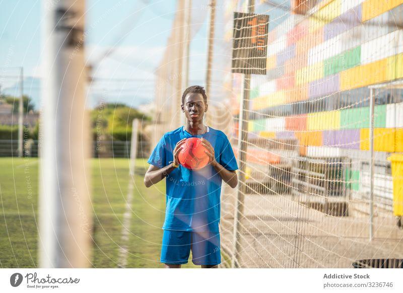 Schwarzer Teenager auf Fussballplatz Fußball Feld Netz Ball Training Sportbekleidung ethnisch Gras männlich Jugendlicher Rasen sonnig tagsüber schwarz