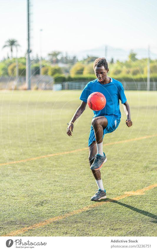 Ethnischer Teenager jongliert mit Fussball Fußball Ball jonglieren Feld Training Spieler Sportbekleidung ethnisch Gras männlich Jugendlicher Knie Rasen sonnig