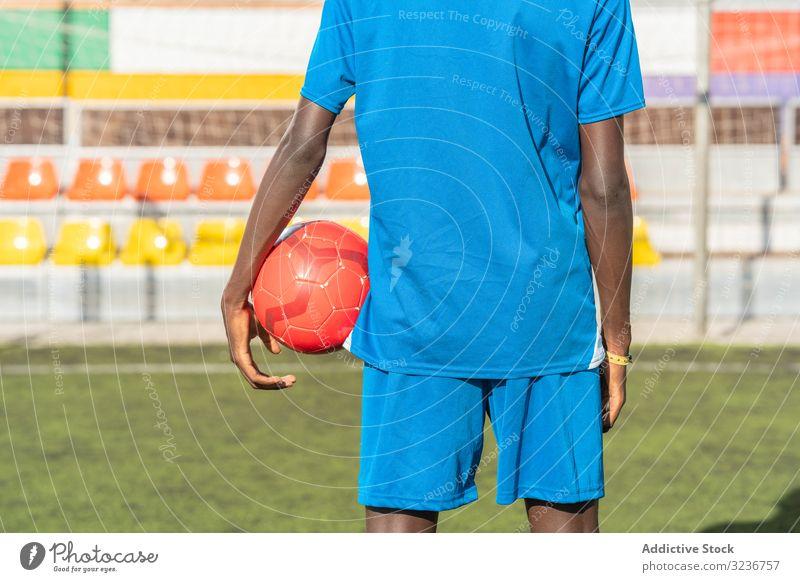 Schwarzer Fussballspieler mit auf dem Stadion stehendem Ball Spieler Fußball Feld Training Sitze Sportbekleidung ethnisch Gras männlich Rasen Netz sonnig