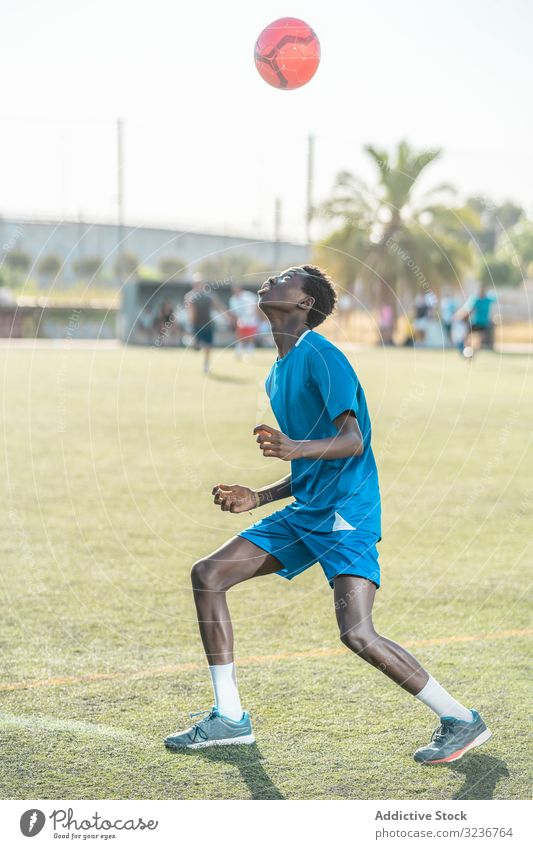 Dünner schwarzer Teenager jongliert Fussball auf dem Kopf Fußball Ball jonglieren Feld Training Spieler Sportbekleidung ethnisch Gras männlich Jugendlicher