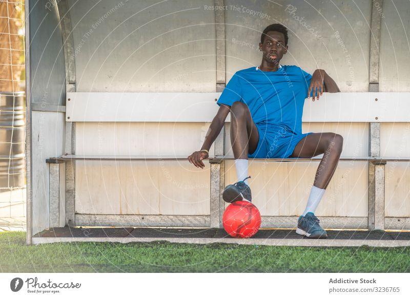 Schwarzer Fussballspieler ruht auf der Bank Teenager Fußball Feld sitzen Pause Ball Training Sportbekleidung ethnisch männlich Jugendlicher sonnig tagsüber