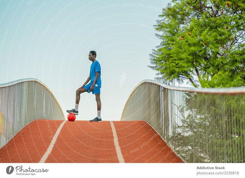 Ethnischer Fussballspieler steht auf dem Weg Fußball Training Ball Straße Teenager ethnisch Spiel Errungenschaft Triumph schwarz Afroamerikaner wettbewerbsfähig