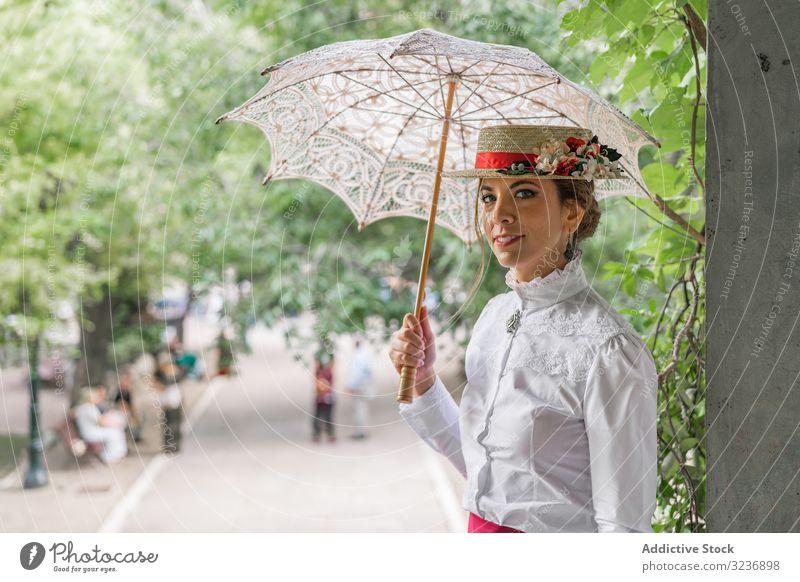 Oldtimer-Dame mit Sonnenschirm im Garten ruhend Frau altehrwürdig Outfit Lächeln Baum Stil elegant grün jung Mode Glück heiter sitzen sich[Akk] entspannen retro