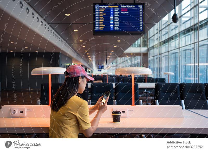 Asiatische Frau surft mit Smartphone, während sie am Tisch unter einer brennenden Lampe Kaffee trinkt Browsen Einwegbecher benutzend Getränk asiatisch