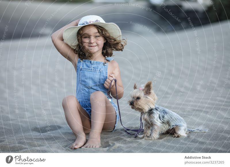 Süßes Mädchen mit Hut in der Hand und mit Hund am Strand sitzend Haustier Sand Sommer MEER Tier Freundschaft Begleiter Urlaub Spaß Ufer Natur windig