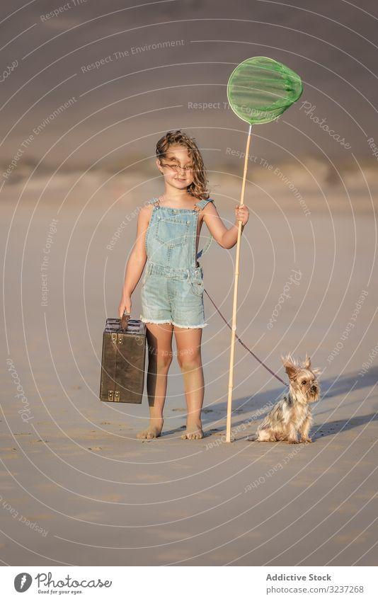 Neugieriges Kind mit Koffer und Schmetterlingsnetz auf Sand stehend mit Hund Mädchen Sommer MEER Tier Freundschaft Haustier Begleiter Urlaub Spaß Ufer Strand