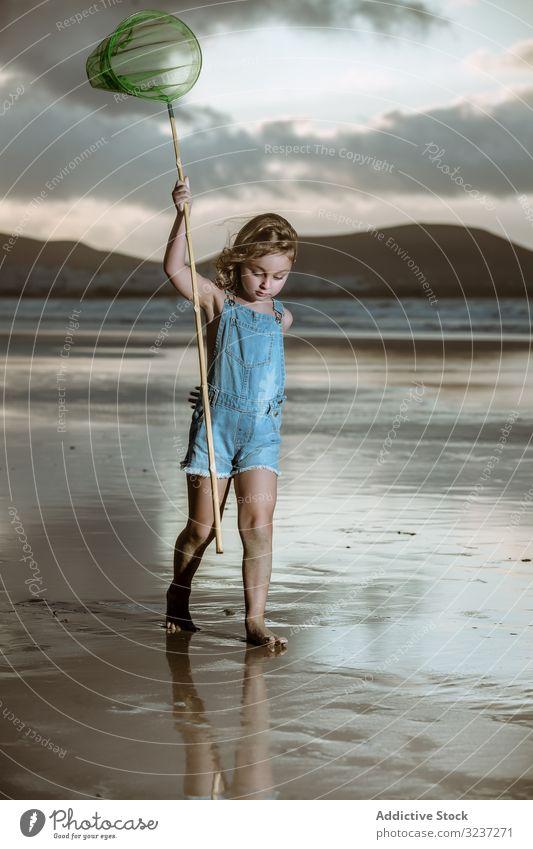 Kurioses Kind mit Schmetterlingsnetz läuft barfuss am nassen Ufer laufen Seeküste niedlich Kindheit Natur fangen Netz Aktivität wenig natürlich Küste Strand