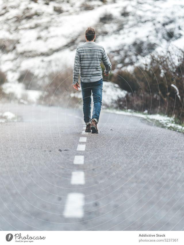 Mann zu Fuß auf der Landstraße Straße wolkig trist Schnee Hügel Spaziergang Wald männlich neblig Erwachsener allein Baum gefroren kalt Natur Erholung ruhen