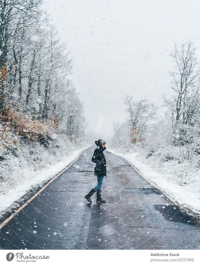 Junge Frau überquert Winterlandstraße Straße Schnee Land neblig wolkig trist Wald Spaziergang jung allein durchkreuzen einsam Baum gefroren kalt Natur Erholung