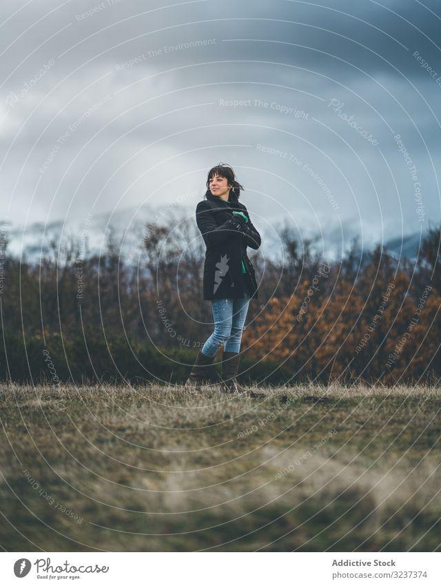 Junge Frau steht im Herbstfeld Feld Land wolkig trist Schnee Hügel Spaziergang Wiese Wald jung allein gefroren kalt Natur Erholung ruhen fröstelnd Reise