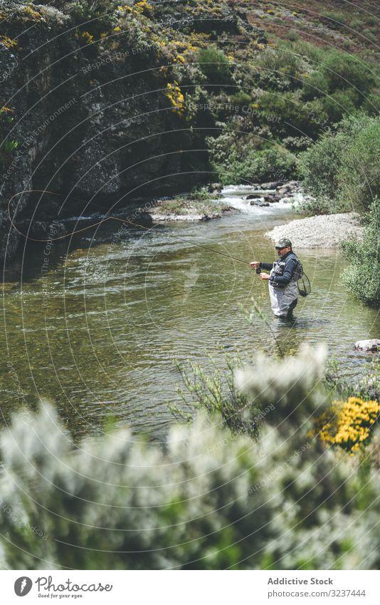 Selbstbewusster Mann fischt mit der Angelrute, während er im Flussstrom steht Fischen strömen selbstbewusst Stab Gerät harling stehen Watvögel Berge u. Gebirge