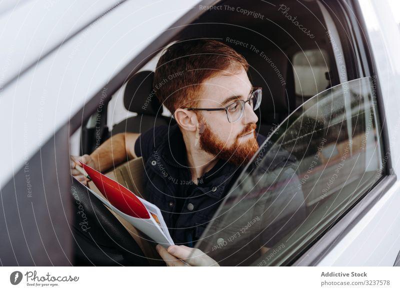 Kurier füllt Papiere aus, während er die Auslieferung der Bestellung an den Kunden im Auto vorbereitet PKW besetzen Versand achtsam Mann schreiben nachdenklich